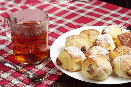 covert: Small cakes with raisins in plate and tea cup on table covert red tablecloth Stock Photo