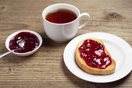 strawberry jam sandwich: White bread with jam and tea cup on rustic wooden table