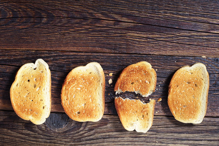 bread: Three slices toasted bread and one ripped on dark wooden background, top view