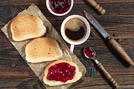 wooden table top view: Bread with jam and coffee cup for breakfast on rustic wooden table, top view Stock Photo
