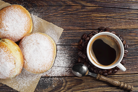Sweet donuts sprinkled with powdered sugar and coffee cup on wooden table, top view