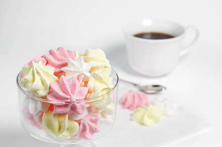 Colorful meringue cookies and cup of hot coffee on white background