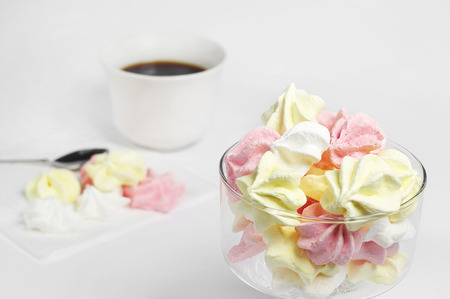 Meringue cookies and cup of coffee on white background Stock Photo