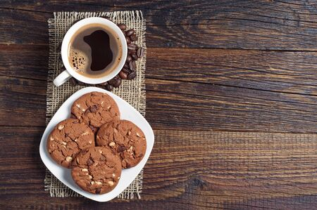 wooden table top view: Cup of hot coffee and chocolate cookies with nuts on wooden table, top view