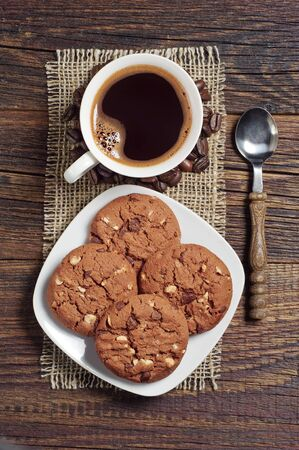 wooden table top view: Chocolate cookies with nuts and cup of hot coffee on wooden table, top view Stock Photo