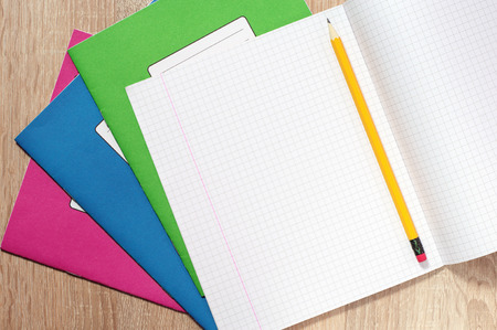 writing materials: Opened school notebooks and pencils on the desk