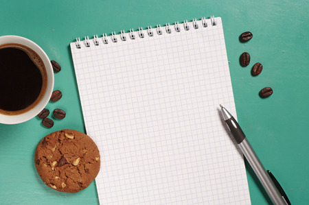 papier lettre: Coffee with cookie and opened notepad on desk from above