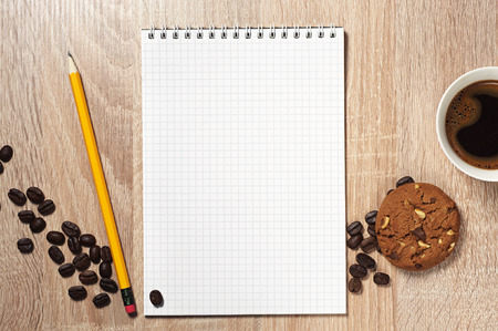 wooden table top view: Opened notepad, coffee and cookie on wooden table, top view