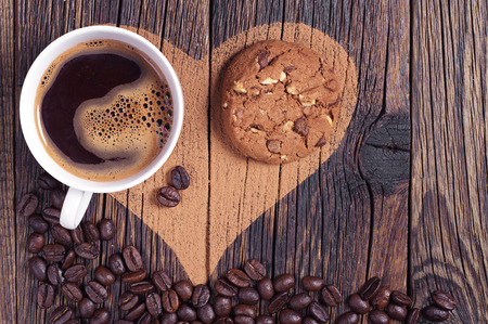 Cup of coffee, chocolate cookie and heart on wooden background, top view