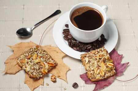 covert: Cup of hot coffee and cookies with nuts on table covert tablecloth