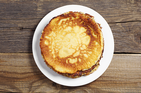 Fried pancakes in plate on rustic wooden table, top view