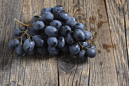 Ripe dark grapes on old wooden table