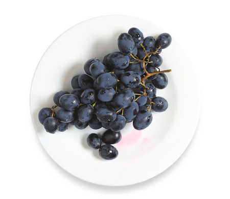 racimos de uvas: Uvas oscuras en plato sobre un fondo blanco