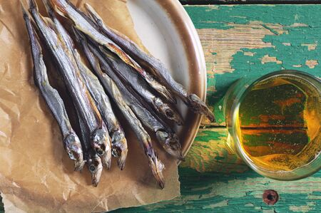 wooden table top view: Dried salted capelin and a glass of beer on vintage wooden table, top view