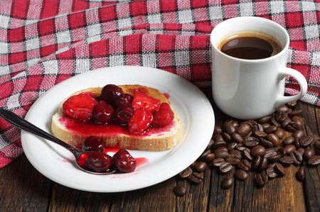 strawberry jam sandwich: Toasted bread with canned cherries, strawberries and cup of coffee on rustic wooden table