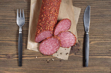 salami slices: Sausage salami slices and cutlery on old wooden table, top view Stock Photo