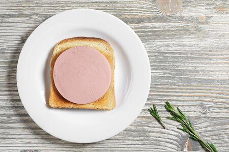 bocadillo: Sándwich con pan tostado y jamón cocido en la vieja mesa de madera, vista desde arriba Foto de archivo