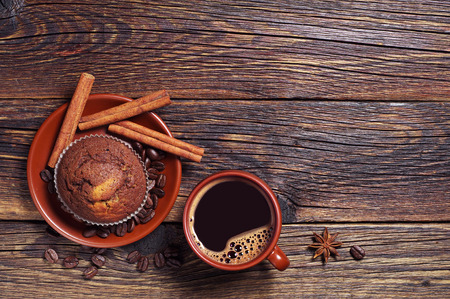 Chocolate cupcake and cup of hot coffee on dark wooden background, top view