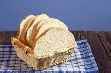 Pan blanco de mimbre en el recipiente de madera sobre la mesa rústica Foto de archivo