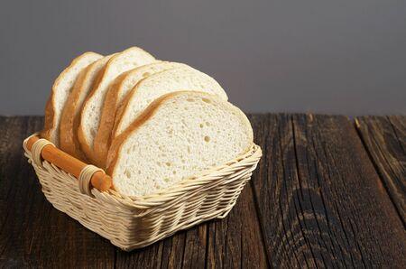 Pan blanco en cuenco de madera de mimbre en mesa rústica