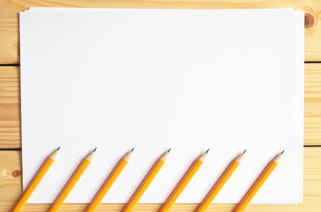 hoja en blanco: Siete lápices y una hoja de papel en blanco en la mesa de madera, vista desde arriba Foto de archivo