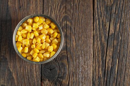 vegetable tin: Canned corn in an iron jar on wooden background, top view Stock Photo