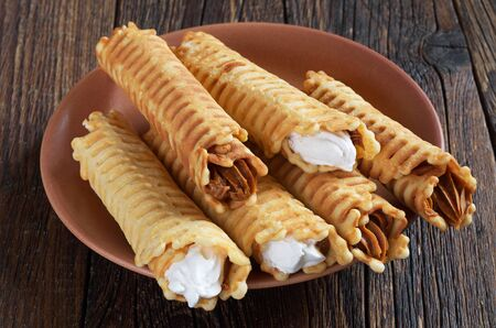 tubules: Waffle tubules with creamy in plate on dark wooden table