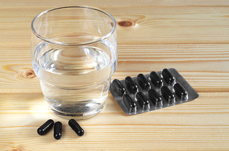 activated: Medical capsules with activated charcoal and glass of water on wooden table