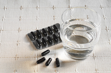 activated: Medical capsules with activated charcoal and glass of water on tablecloth