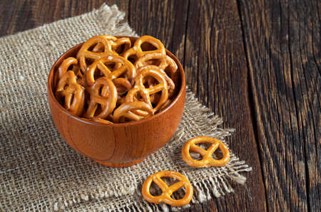 snacking: Small salted pretzels in bowl on wooden table Stock Photo
