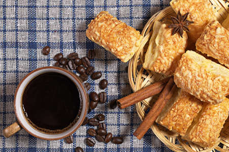 snacking: Cup of hot coffee and cookies with cheese on blue tablecloth, top view