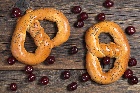 pretzel: Pretzels with poppy seeds and cherry on wooden background, top view