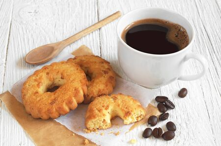 snacking: Cup of hot coffee and cookies rings with nuts on white wooden table