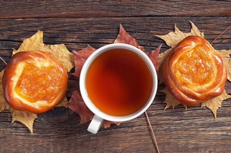 snacking: Cup of tea and buns with apricot jam on dark wooden table, top view