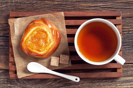 snacking: Cup of tea and bun with jam on old wooden table, top view Stock Photo