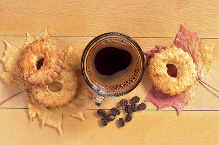 snacking: Cup of hot coffee and cookies with nuts on yellow wooden table, top view