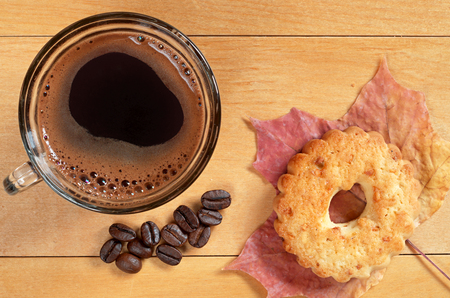 snacking: Cup of hot coffee and cookies with nuts on yellow wooden table closeup, top view