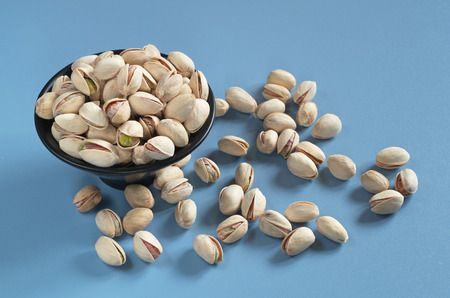 Pistachios nuts in black bowl and near on blue table Reklamní fotografie