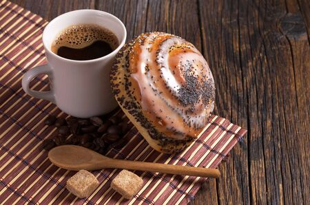 Cup of coffee and fresh bun with poppy seeds on dark wooden table Stock Photo