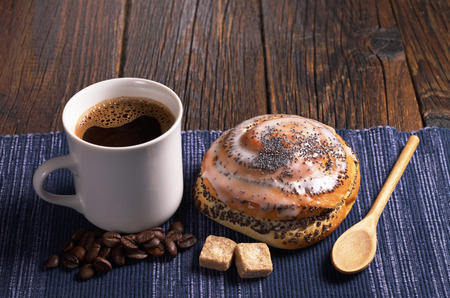Cup of coffee and delicious bun with poppy seeds on rustic wooden table Stock Photo