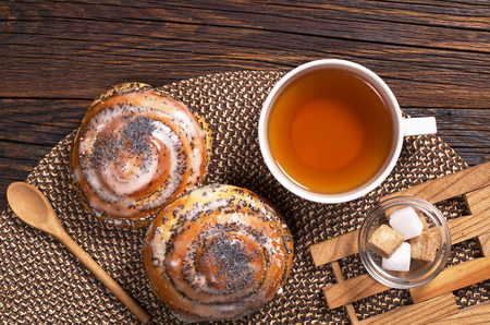 Two delicious buns with poppy seeds and cup of tea on rustic wooden table, top view
