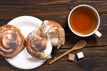Cup of tea and tasty buns with poppy seeds on old wooden table, top view Stock Photo