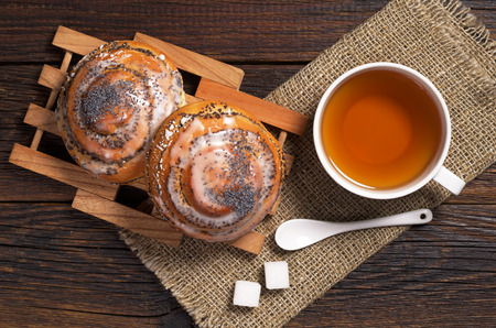 Two sweet buns with poppy seeds and cup of tea on dark wooden table, top view