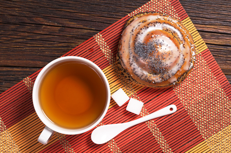 Cup of tea and tasty bun with poppy seeds on wooden table, top view