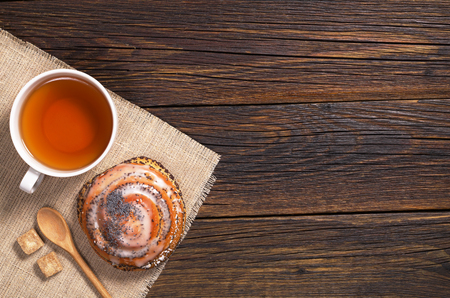 Cup of tea and bun with poppy seeds on wooden table, top view. Space for text Stock Photo