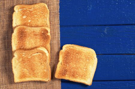 Slices of toasted bread on blue wooden table, top view