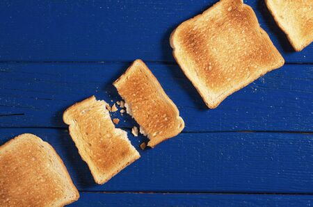 Slices of toasted bread on blue wooden table close up, top view