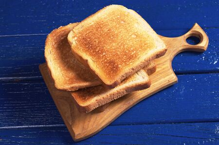 Slices of toasted bread on blue wooden table close up