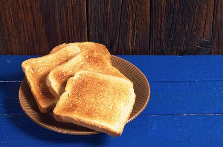 Slices of toasted bread in plate on blue wooden table