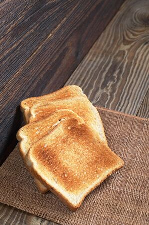 Slices of toasted bread on old wooden table. Vertical photo Stock Photo